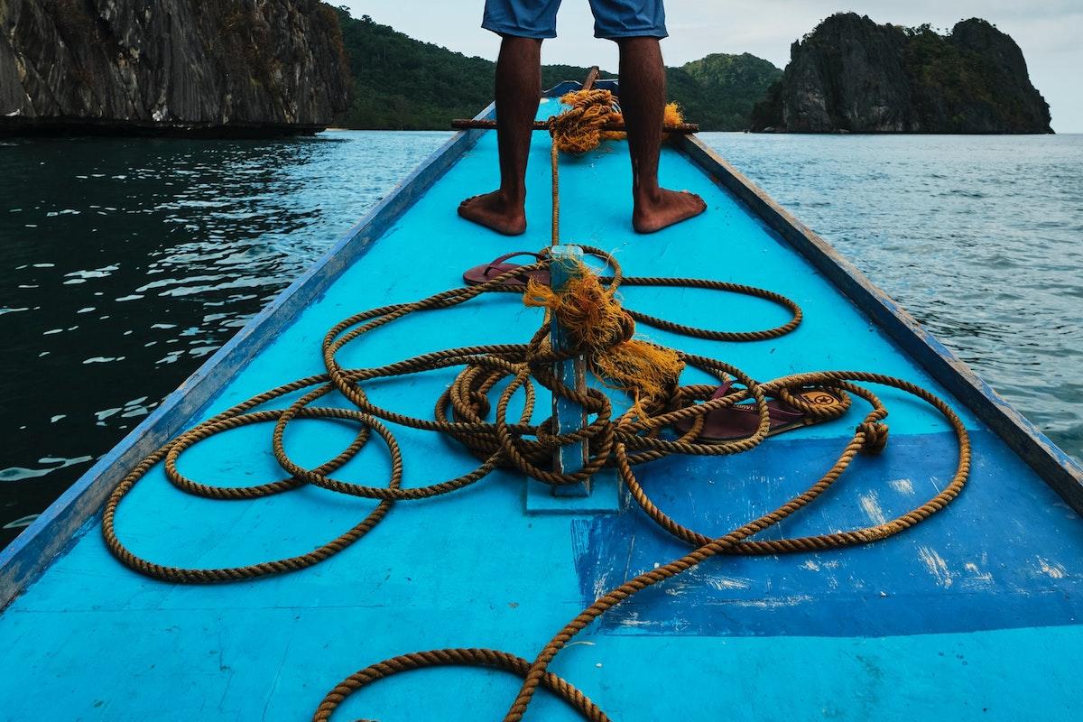 Homem em pé na proa de bote